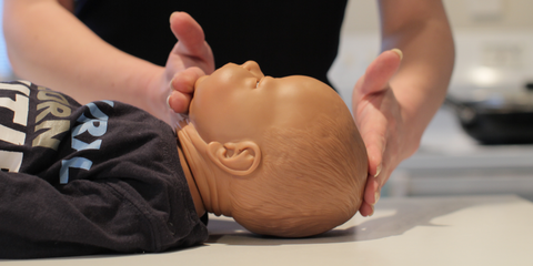Practising first aid scenarios on a baby mannequin
