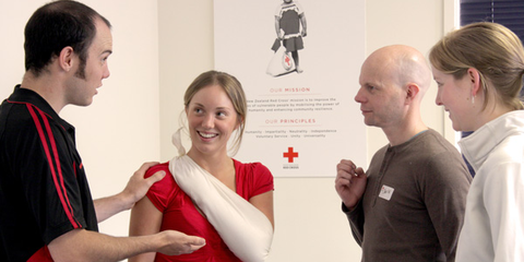 Comprehensive first aid - demonstrating putting an arm in a sling