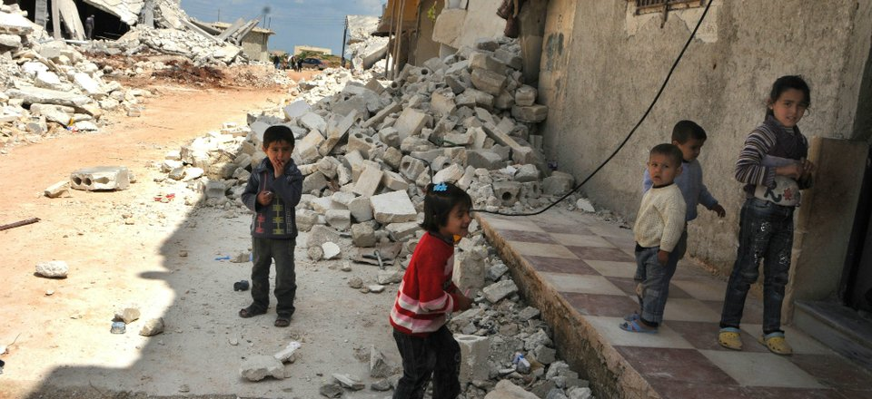 Children play amongst rubble caused by an explosive weapon in Syria