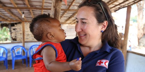 A Red Cross aid worker holds a child