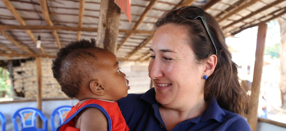 Chelsea, a Red Cross aid worker, meets a child in Kenya.