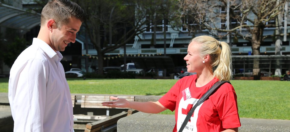 A Red Cross campaigner chats to a potential donor in the street