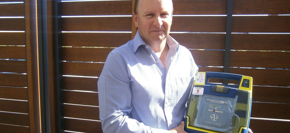 Cardiac arrest survivor Jeff Cox with a Red Cross AED.