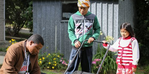 Refugee volunteers helping out a former refugee with gardening