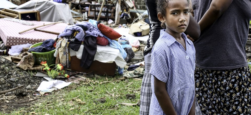 A girl in Rakiraki stands outside a home torn apart by Cyclone Winston