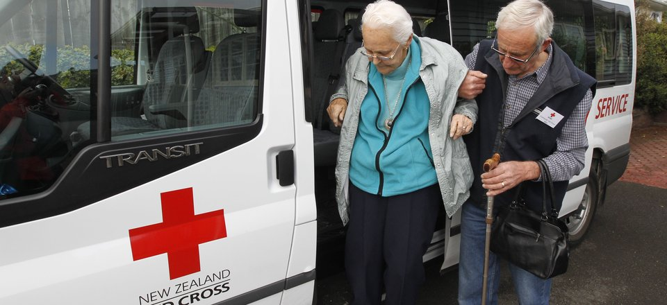 Community transport driver helps a lady out of the van
